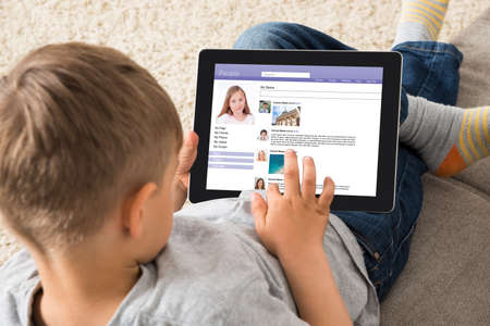 social networking: Close-up Of Boy Using Social Networking Site On Digital Tablet At Home Stock Photo