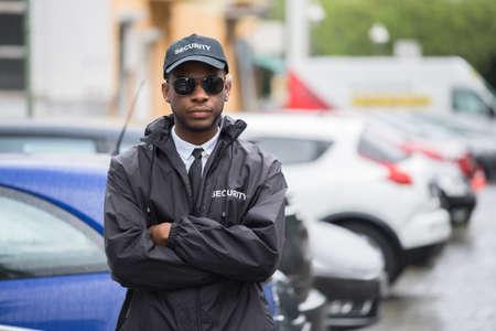 Retrato de joven africana Guardia de seguridad masculino en brazos cruzados uniforme de pie en la calle