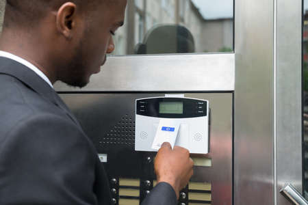 keycard: Close-up Of Young African Businessman Using Keycard To Open Door