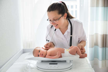 Happy Female Pediatrician Checking Weight Of Cute Baby Stock fotó - 60368630