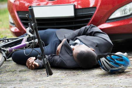 Jóvenes africanos Ciclista masculino acostado en la calle después del accidente