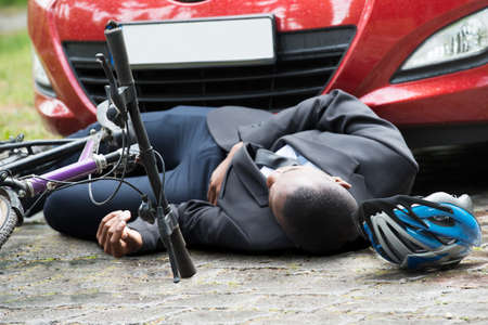 Young African Male Cyclist Lying On Street After Accident