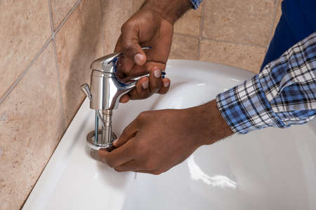 installing: Close-up Of Male Plumbers Hand Fixing Tap Of Sink