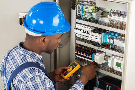 circuito electrico: Jóvenes africanos Técnico de sexo masculino que examina Fusebox con el multímetro Sonda