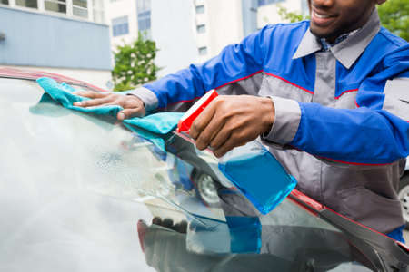car glass: Young Male Worker Cleaning Car Windshield With Cloth And Spray Stock Photo