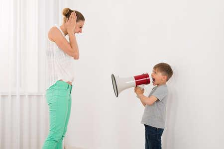 comunicarse: Niño gritando a su madre a través del megáfono