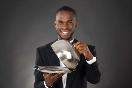 servings: Portrait Of Happy Waiter Serving Meal In Cloche