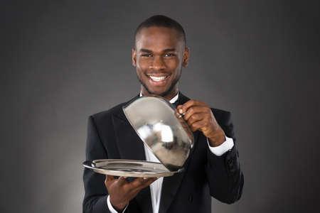 Portret szczęśliwy kelner serwuje posiłek w Cloche