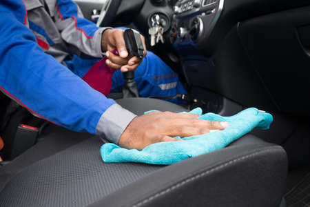Close-up Of A Male Worker Cleaning Seat Inside The Car Archivio Fotografico