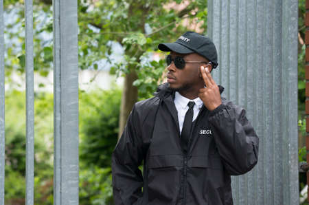 earpiece: Young African Male Security Guard Listening To Earpiece