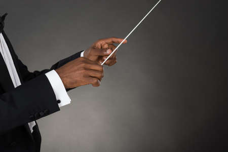 choral: Close-up Of Music Conductor Hands Holding Baton Stock Photo