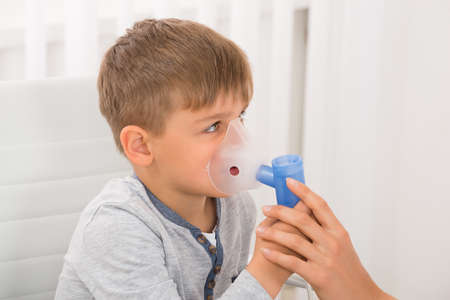 inhaling: Close-up Of A Little Boy Inhaling Through Oxygen Mask In Clinic Stock Photo