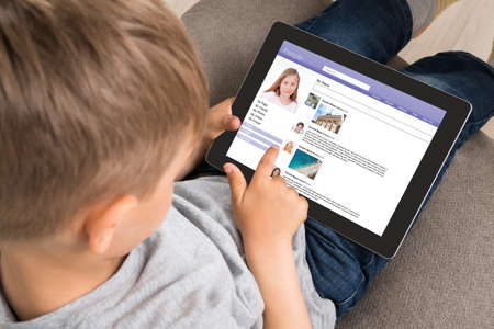 Close-up Of Cute Little Boy Using Social Networking Site On Digital Tablet At Home Stockfoto