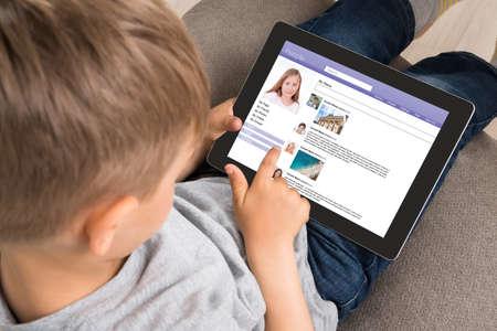 Primer Del Niño lindo que usa el sitio de redes sociales en Tableta digital en el hogar Foto de archivo
