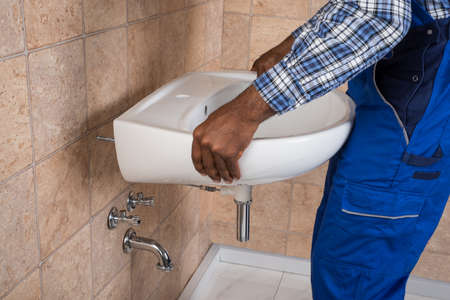 maintenance fitter: Close-up Of Young African Handyman Fixing Sink In Bathroom Stock Photo