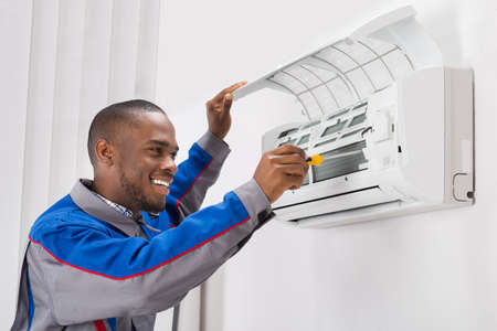 Happy Young African Male Technician Repairing Air Conditioner Imagens