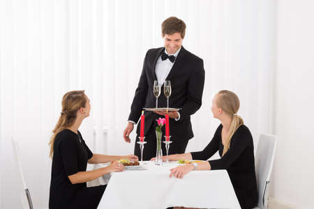 servings: Happy Waiter Serving Glass Of Champagne To Female Friends In Restaurant With Food On Table Stock Photo