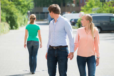 celos: Grito de la mujer joven a su novio, mirando a otra mujer en la calle