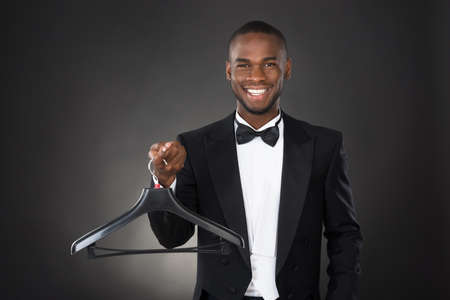 black male: Portrait Of Happy Male Housekeeper Holding Plastic Hanger Stock Photo