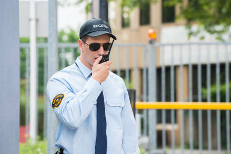 security guard: Primer De La Guardia de seguridad masculino que habla en el walkie-talkie