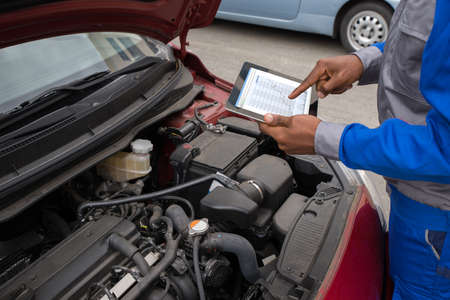 Close-up-Mechaniker mit digitaler Tablette Graph zeigt, während Auto Untersuchen