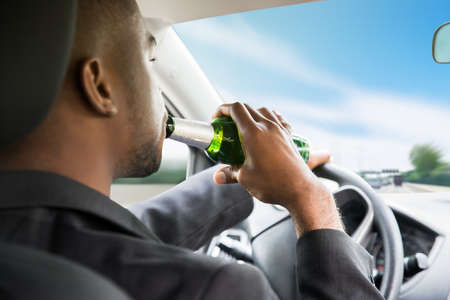 drinking driving: Side View Of A Young African Businessman Drinking Beer While Driving Car