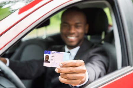 Happy Young African Businessman Showing His Driving License From Open Car Window Stock Photo