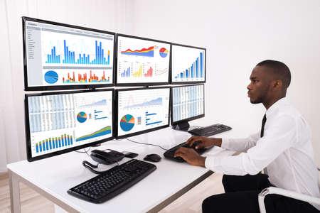 青年実業家のオフィス内の複数のコンピューター上の金融チャートを分析