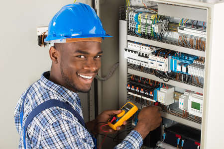 Young African Male Techniker Untersuchen Fusebox mit Multimeter Probe