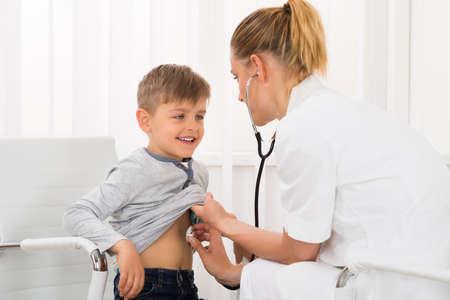 stethoscope boy: Female Doctor Examining Boy With Stethoscope In Clinic