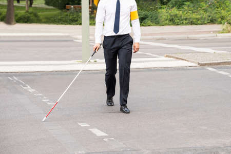 cross street with care: Blind Person With White Stick Walking On Street Stock Photo