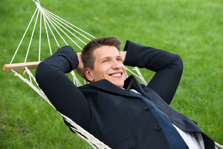 people relax: Happy Young Businessman Lying In Hammock At Park Stock Photo