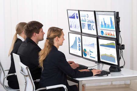 computer screens: Young Male And Female Businesspeople Looking At Financial Graphs On Multiple Computers In Office Stock Photo