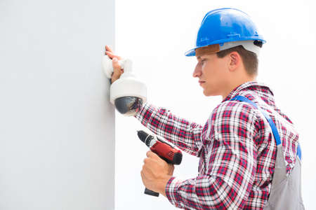setup man: Young Male Technician Installing Camera On Wall Using Electric Cordless Drill Stock Photo