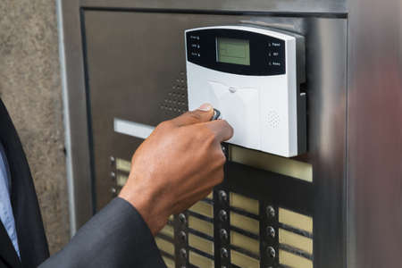 businesspersons: Close-up Of Businesspersons Hand Using Remote Control For Operating Door Security System