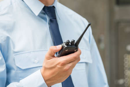 Close-up Photo Of Security Guard Holding Walkie-talkie Zdjęcie Seryjne