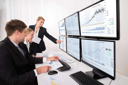 multiple: Happy Young Stock Market Brokers Looking At Graphs On Multiple Computer In Office