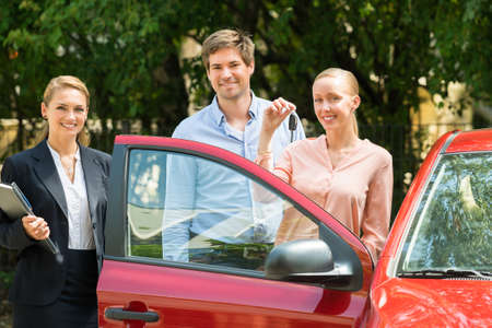 purchased: Dealer Standing Besides Happy Young Couple With Key Of Newly Purchased Car