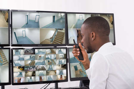 security room: Male Operator Talking On Walkie-Talkie While Looking At CCTV Footage