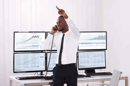 stock trader: Male Stock Trader Pointing Upwards While Talking On Telephone