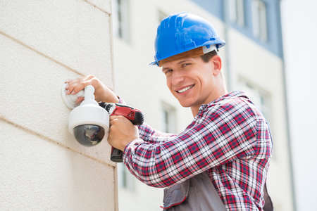 adjusting: Young Male Technician Installing Camera On Wall Using Electric Cordless Drill Stock Photo