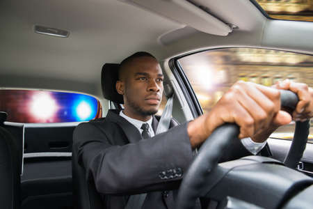 Young African Businessman Chased By Police While Driving Car Stock Photo