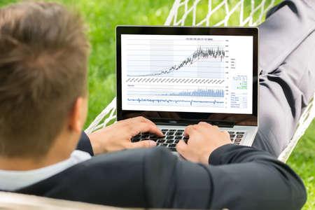 stock: Close-up Of Male Stock Broker Lying In Hammock Using Laptop
