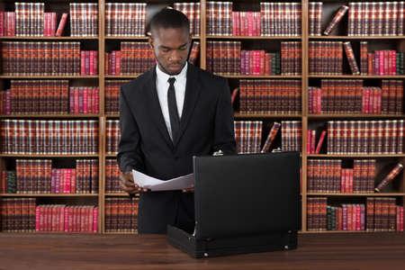 abogado: Abogado de sexo masculino con papeles y Maletín en el escritorio en la oficina