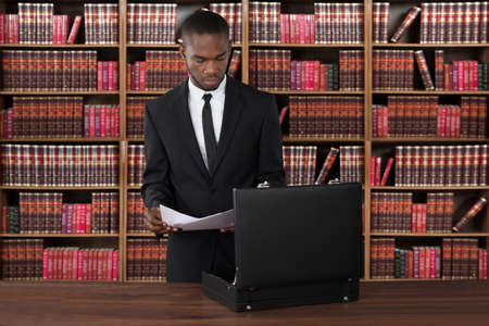 attorney: Male Lawyer With Papers And Briefcase At Desk In Office Stock Photo