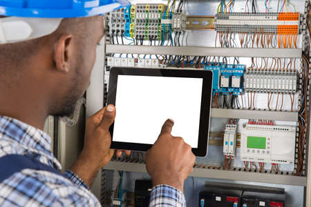 Close-up de jeune technicien Homme africain Utilisation Tablette numérique Bien examen Fusebox