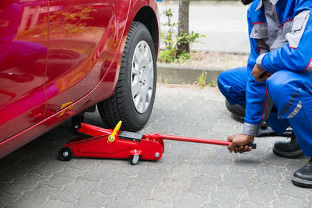 lifting jack: Young Male Mechanic Putting Red Hydraulic Floor Jack Inside The Car Stock Photo