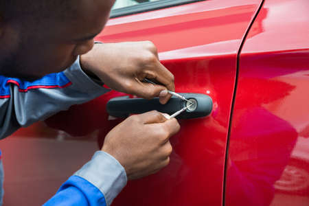 Young Male Mechanic Holding Lockpicker To Open Red Car Door Stockfoto