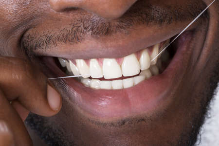 Close-up Of An African Man Cleaning His Teeth With Floss