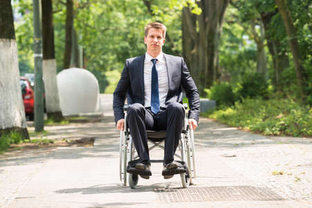 young man portrait: Portrait Of Young Happy Disabled Man On Wheelchair Stock Photo